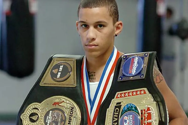Miguel Cartagena shows off his championship medal and belts. (Sarah J. Glover/Staff Photographer)