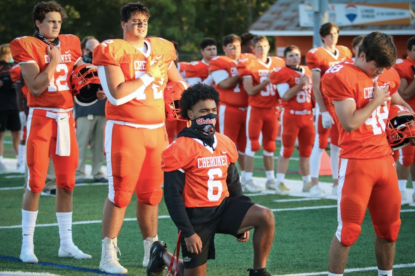 Cherokee football player kneels for national anthem to protest racial injustice