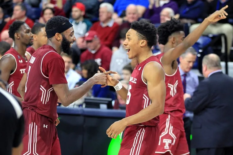 Josh Brown, 2nd from left, and Nate Pierre-Louis, 3rd from left, of Temple celebrate as they go off the court after their 60-51 victory over Penn at the Palestra on Jan 20, 2018.