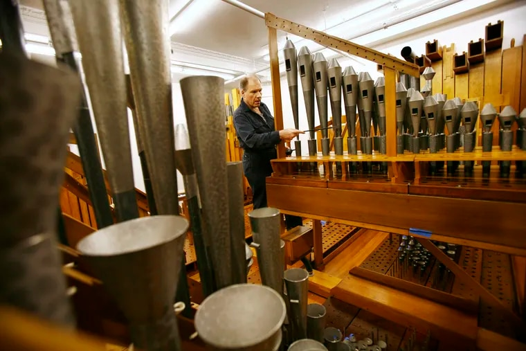 Peter Batchelder (chief of tuning) tunes the French horn in the orchestral chamber of the Wanamaker organ at Macy's in Center City in 2008.