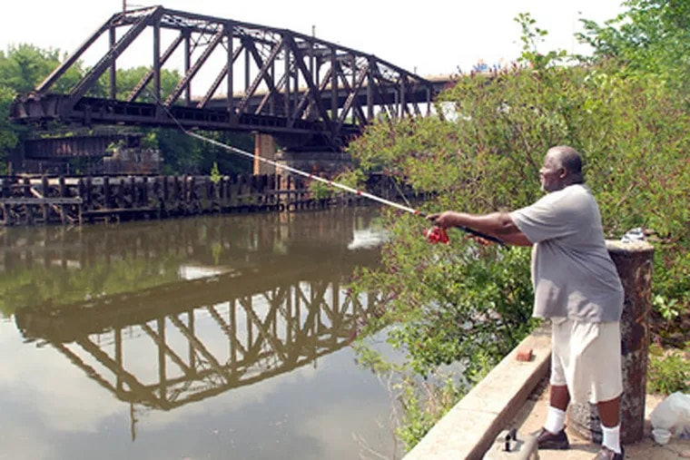 Near Bartram's Garden, Dennis Randolph casts a line into the Schuylkill near the southern boundary of the so-called DuPont Crescent tract. The two new tracts will help connect this point with Locust Street. (Ron Tarver / Staff Photographer)