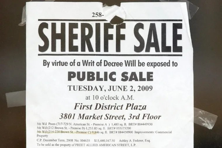 A sheriff sale notice is taped to a window in May 2009.