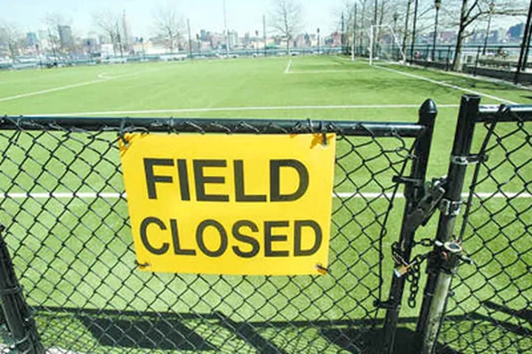 An artificial turf soccer field lay behind a locked gate at a park in Hoboken, N.J., last year. This field and another were closed because state health officials found high levels of lead dust. (MIKE DERER / Associated Press)