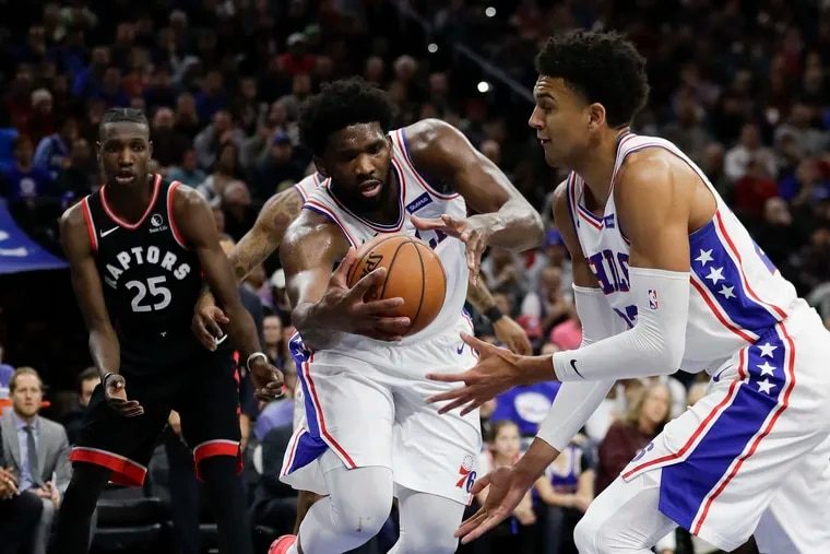 Sixers center Joel Embiid grabs the basketball next to teammate Matisse Thybulle (right) against the Raptors.