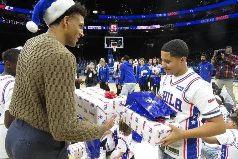 Sixers rookie Matisse Thybulle hands a gift to Yaniel Santiago Delgado of the Boys and Girls Club of Chester. The Sixers hosted 20 youngsters before Friday's game against the Dallas Mavericks and surprised them by giving them gifts.