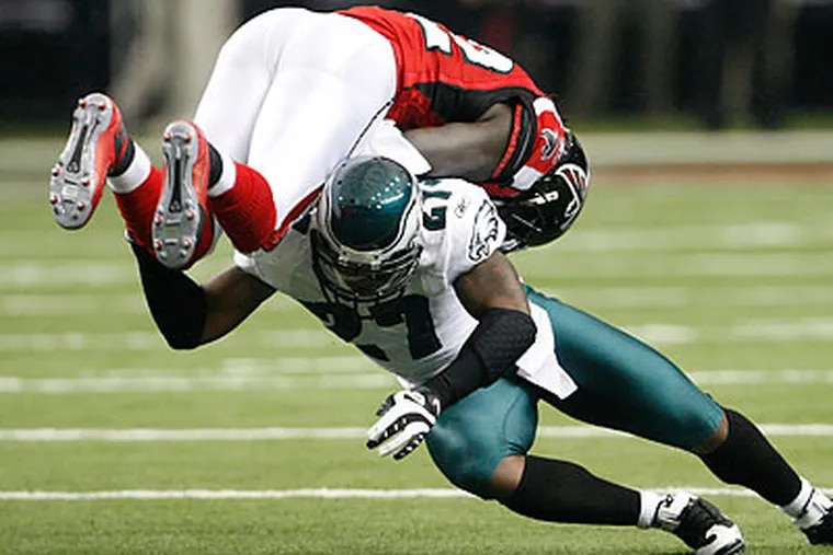 The Eagles' defense had a strong game against the Falcons, including this tackle of Atlanta's Jerious Norwood by Quintin Mikell during the first quarter. (Ron Cortes/Staff Photographer)