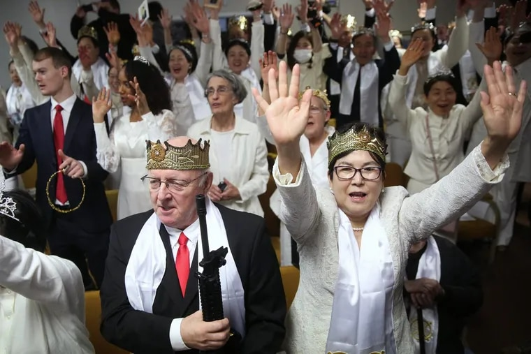 A couple who didn't want to give their names cheers at the end of a marriage blessing ceremony while holding a rifle at Sanctuary Church in Newfoundland, Pa., on Wednesday, Feb. 28, 2018.