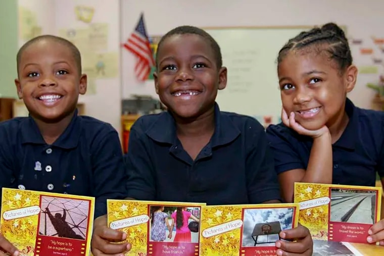 """From left to right, Tae'Marr Tubbs, 5 Logan Reed, 6, and Asia Pagan, 6, hold up the greetings cards that were made with their photos and words of inspiration. They are called """"Pictures of Hope"""". A few children at one of the city's homeless shelters took pictures with donated cameras - pictures about their lives. Pictures of Hope, as they are dubbed. Those snapshots have now been turned into cards, available as a fundraiser for Drueding Center, a homeless shelter. 10/15/2014 ( MICHAEL BRYANT  / Staff Photographer )"""