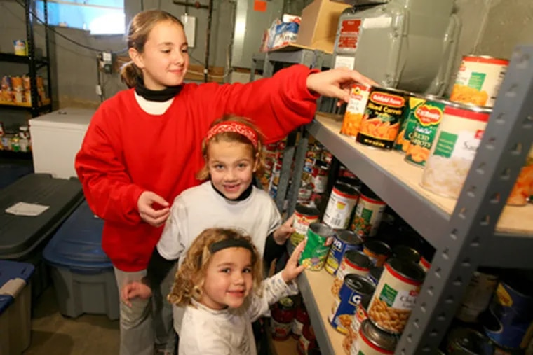 Buss sisters (from back) Anna, Grace, and Abigail stock Bridge of Peace Community Church's pantry in Camden. (Charles Fox / Staff Photographer)