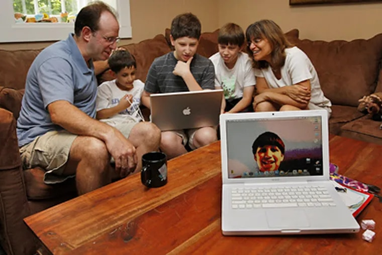 """Ari Weinstein (center) at home in Mount Airy demonstrates his computer wizardry for (from left) father Ken, brothers Noah, 8, and Evan, 12, and mother Judy. Says a teacher: """"Ari is unusual in that his skill set is fairly narrow but really deep."""" (Michael S. Wirtz / Staff Photographer)"""