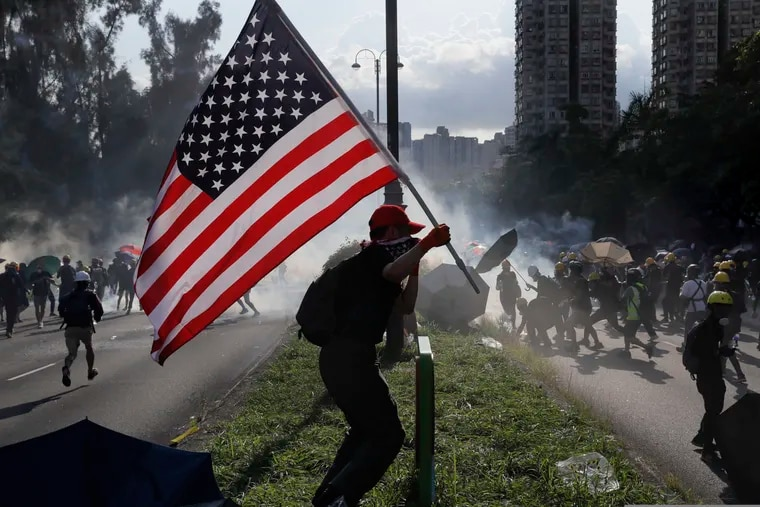 FILE - In this Aug. 5, 2019, file photo, a protester runs with a United States flag as tear gas are released on protesters in Hong Kong. China's central government has dismissed Hong Kong pro-democracy protesters as clowns and criminals while bemoaning growing violence surrounding the monthslong demonstrations. (AP Photo/Kin Cheung, File)