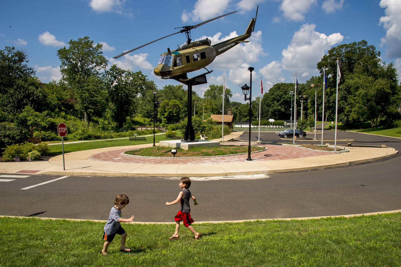 Noah (left, 3) and Nate Kolsky, 5, pretend to be airplanes, playing near the memorial.