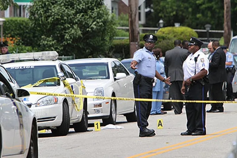 Investigators gather on the 7900 block of Rugby Street in the Stenton section of Philadelphia, on Friday, where police shot and killed SEPTA bus driver Eric Crawley, 39. (Joseph Kaczmarek / For the Inquirer & Daily News)