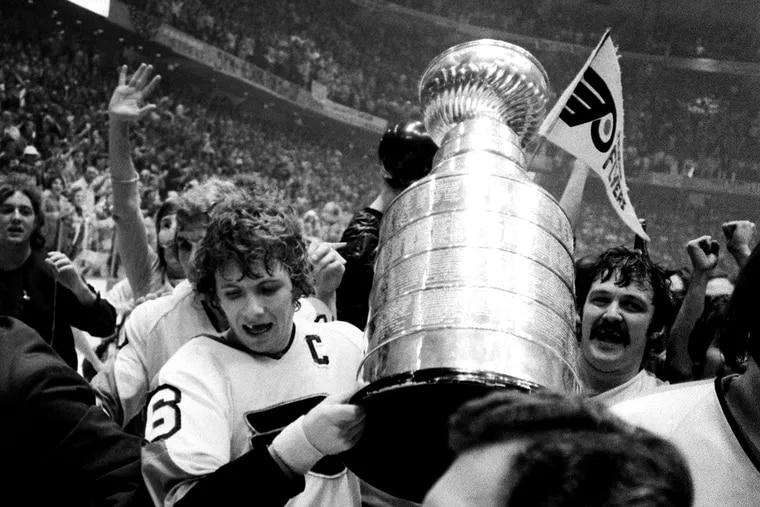 With fans climbing the glass and joining the celebration, Flyers captain Bobby Clarke, left and goalie Bernie Parent, right, skate the Stanley Cup around the Spectrum ice after defeating the Boston Bruins, 1-0, in Game 6 on May 19, 1974.