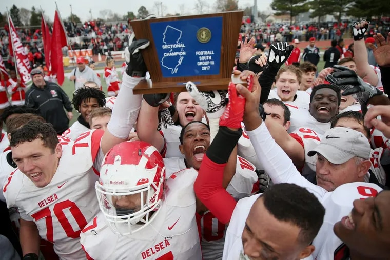 Delsea players celebrate with the South Jersey Group 3 championship trophy after defeating Woodrow Wilson 29-28 at Rowan University.