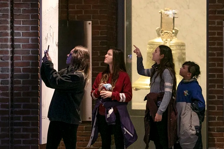 On a trip to Philadelphia from their home in Sacramento, Calif., Joanna Hurtt (left) takes a photo of Independence Hall as the clock strikes 5 p.m. Sunday, while her kids Jazi, Julia, and Jace look on. The coronavirus has forced the closure of all historic sites on Independence Mall, as well as other local attractions, through at least Jan. 1.