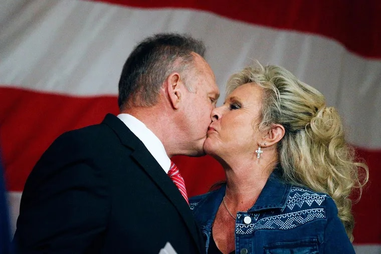 Former Alabama Chief Justice and U.S. Senate candidate Roy Moore kisses his wife, Kayla Moore, after speaking at a Dec. 5 campaign rally  in Fairhope, Ala.