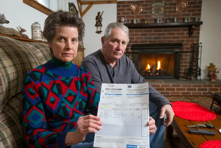 Leslie Prahar and Dave Southard show the medical bill they disputed for seven months in their home in Broomall, Pa.
