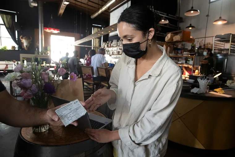 Olivia Caceres, general manager at Martha, checks a customer's vaccination card. Proof of vaccination is needed to dine inside. Patrons without proof can still dine outside.