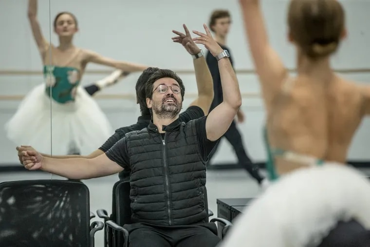 """Pennsylvania Ballet artistic director Angel Corella (seated) works with principal dancer Oksana Maslova (right and reflected in the mirror) as they rehearse """"The Sleeping Beauty,"""" which opens the season Thursday."""