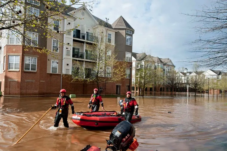 Rescue workers check for debris at the Riverview Landing apartments in West Norriton. By Thursday morning, several feet of water stood in the parking lot as residents looked down from their balconies. Those who wanted to go to work had to leave via small boats manned by marine rescue crews.