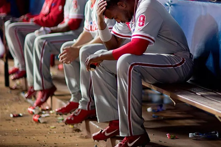 Philadelphia Phillies' Domonic Brown sits in the dugout after striking out in the fifth inning of a baseball game against the Atlanta Braves, Thursday, Sept. 26, 2013, in Atlanta. (AP Photo/David Goldman)