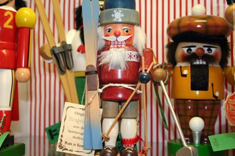 """This Nov. 11, 2012 photo shows a variety of Nutcracker dolls at The Whitney Shop In New Canaan, Conn. The wooden dolls, many of which will really crack your walnuts and macadamias, are increasingly popular in holiday decor. The classic Nutcracker nutcracker, a soldier with his sword in hand and prominent moustache, comes from the early 19th-century tale """"The Nutcracker and the Mouse King.""""  (AP Photo/Samantha Critchell)"""