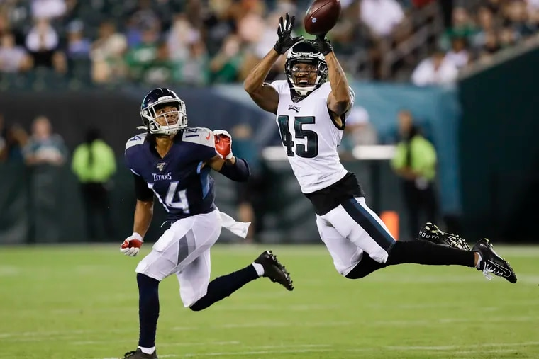 Eagles cornerback Orlando Scandrick leaps after the football against Titans wide receiver Kalif Raymond during the preseason. Raymond caught the deflected football.