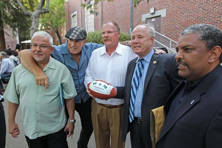 Former Eagles coach and current Chiefs coach Andy Reid (center) stands with former teammates on his John Marshall High School team. From left to right: Jesse Alverez, Richard Carmichael, Reid, Tom LaBonge and Robert Judkins.