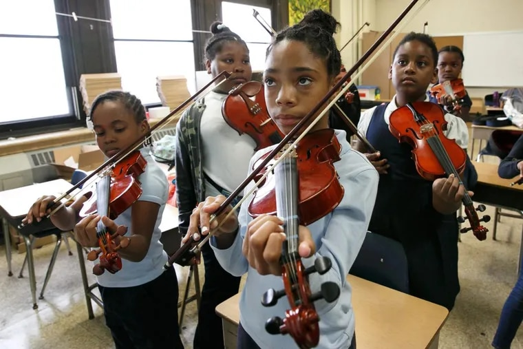 Nevaeh Wright, front center, practices the violin along with her classmates at Mitchell Elementary School, in Philadelphia, Oct. 16, 2017.