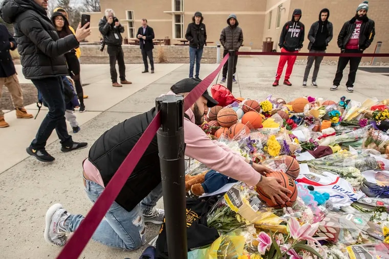 Stephan Sanchez, from Upper Darby, places a basketball where he had written a thank you letter to Kobe Bryant into a memorial in front of Bryant Gymnasium at Lower Merion High School.