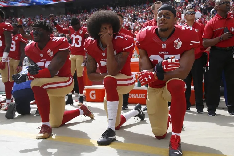From left, the San Francisco 49ers' Eli Harold, Colin Kaepernick and Eric Reid kneel during the national anthem before their NFL game against the Dallas Cowboys on Oct. 2, 2016, at Levi's Stadium in Santa Clara, Calif.