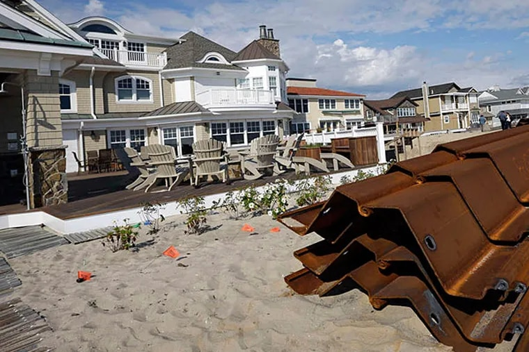 Mantoloking homes that have been restored after Hurricane Sandy rise behind long steel sheets that will be driven into the dunes to make a protective barrier as part of Shore restoration. (Mel Evans/Staff)