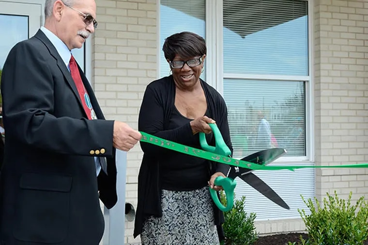 Senior Development Officer of Pennsylvania Housing Finance Agency, William Bailey (left), and resident Lauren Davis (right) cut the ribbon at the groundbreaking ceremony for Anthony Wayne II, the second phase for the energy efficient senior housing complex project located in South Philadelphia July 16, 2014. (VIVIANA PERNOT/ Staff Photographer)