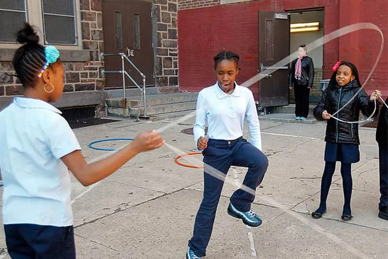 Makiyah Vincent, Tiffany McCormick, and Gianni Davis play jump rope.