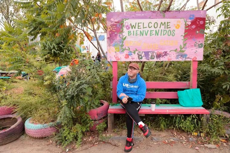 Adam Butler sits at the Cesar Iglesias Community Gardens on Arlington Street in Philadelphia on Sept. 30, 2021.