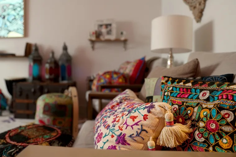 Natalie Jesionka and Ashvin Vijayakumar have filled their Fishtown rowhouse with warmth and color. They've decorated the living room with  pillows in cases collected from travels to places like Thailand, India, Burma, and Poland.