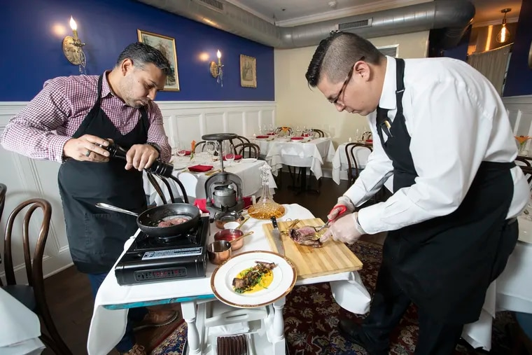 """Ricky Lorenzo, left, and David Sandoval work to prepare a wild wood pigeon """"a la presse"""" in the dining room in June BYOB."""