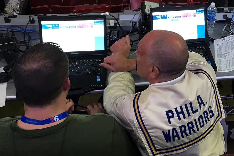 Sixers stat crew chief Ron Pollack wore an authentic Philadelphia Warriors warmup jacket while working at a recent game. Son Brian is to his left. MIKE JENSEN / Staff