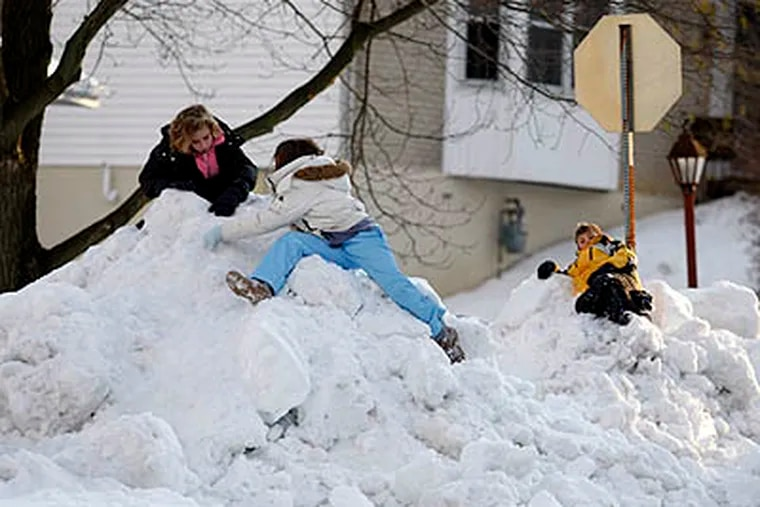 Rachel Mills and Shelby Moore, both 10, and Mitchel Mills, 9, Rachel's brother, took advantage of a snow day and street plowing to form giant snow mountains on Monday, in Claymont, Del. (Ron Cortes / Staff Photographer)