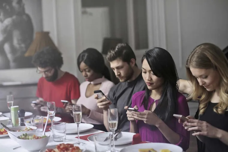 Friends are having dinner together, but everybody is looking at their phones.