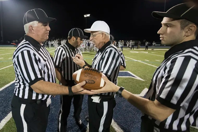 The officials, including referee Bill McKeever (in white hat), gather before the football teams from Episcopal Academy and Malvern Prep play on Oct. 25, 2019.