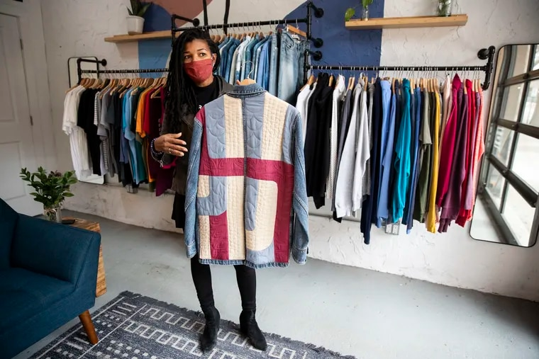 """Kimberly McGlonn, CEO & Founder of Grant BLVD, shows off a jean jacket in her shop at 3605 Lancaster Avenue in West Philadelphia. Described as a """"sustainable, ethical brand,""""  the company sources reclaimed fabrics, manufactures its goods in Philadelphia, and supports social and environmental justice causes."""