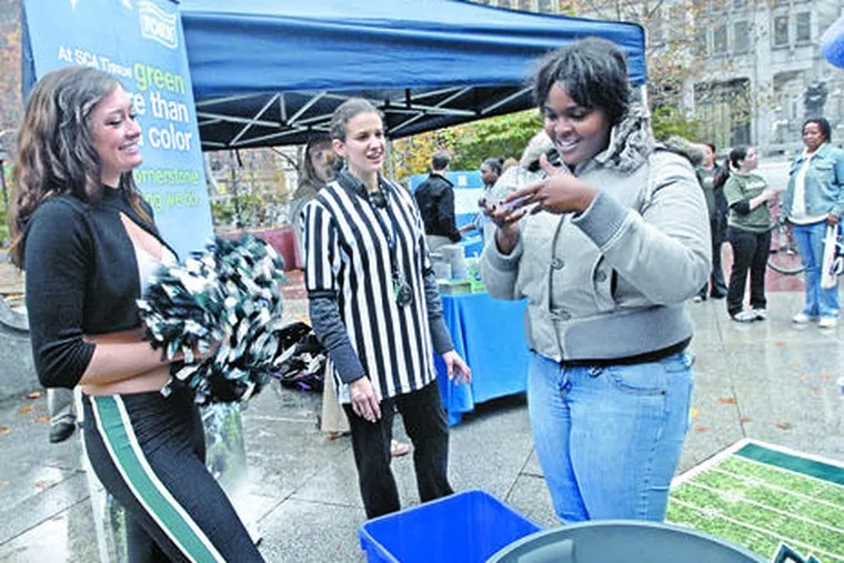 At a JFK Plaza recycling promotion, Eagles cheerleader Tina Thomas (left) and Raquel Carbonari watch as a Philadelphian named Sasha plays a game in which the goal is sorting recyclables.