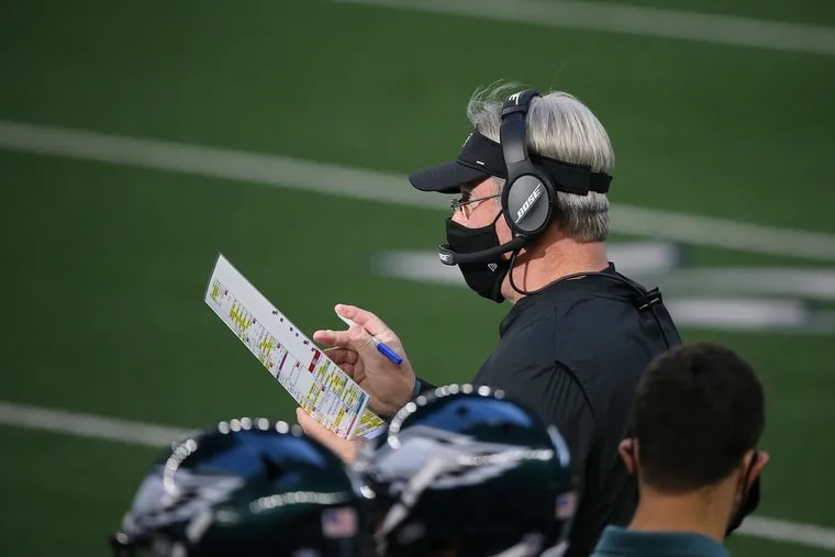Head coach Doug Pederson looks over his play chart during Sunday's 37-17 loss that ended the Eagles' playoff hopes.