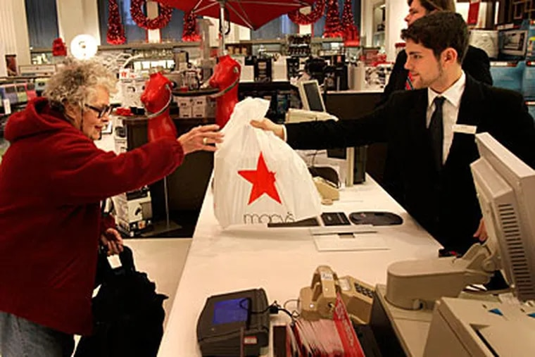 Charlotte Taylor does some early morning Black Friday shopping at the Macy's in center city Philadelphia. At right, sales associate Alex Murphy helps her with her purchases. ( Laurence Kesterson / Staff Photographer )
