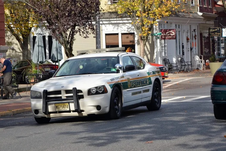 A Bordentown Township Police patrol car rides along Farnsworth Avenue in Bordentown City shortly after the hate crime charges were announced against former Chief Frank Nucera Jr.
