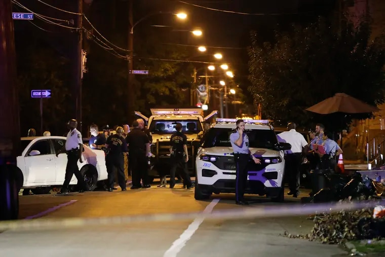 Police officers gather along the 500 block of Dauphin Street in North Philadelphia near where an officer was grazed in the head by a bullet on Monday, August 23, 2021.