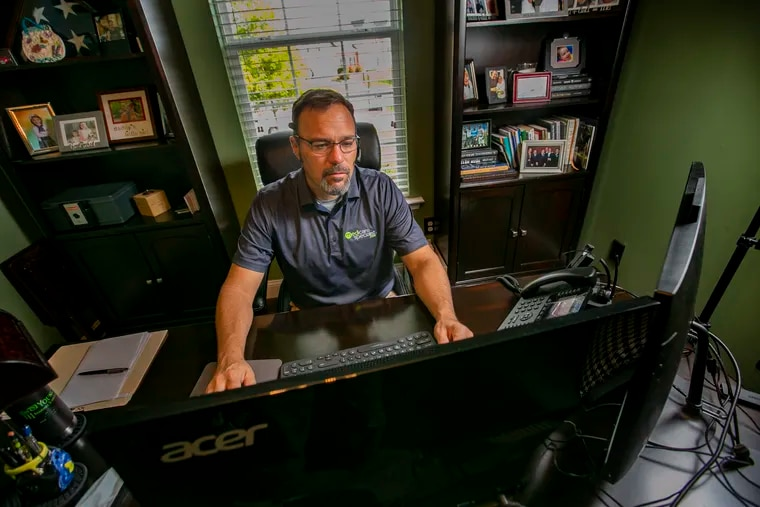 """James Long, a health-care insurance broker at his computer inside his home office in Royersford, helps people that have lost """"job-based health insurance"""" during the COVID-19 pandemic."""