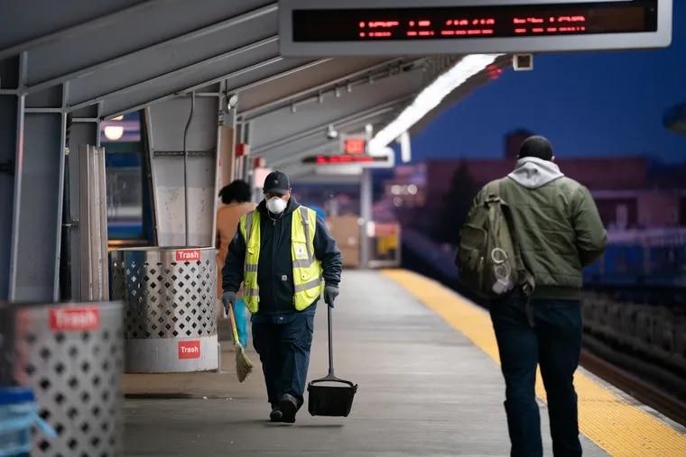 SEPTA worker Ervin Lavenhouse wears a mask as he works sweeping up trash on the platform at the 52nd Street station.